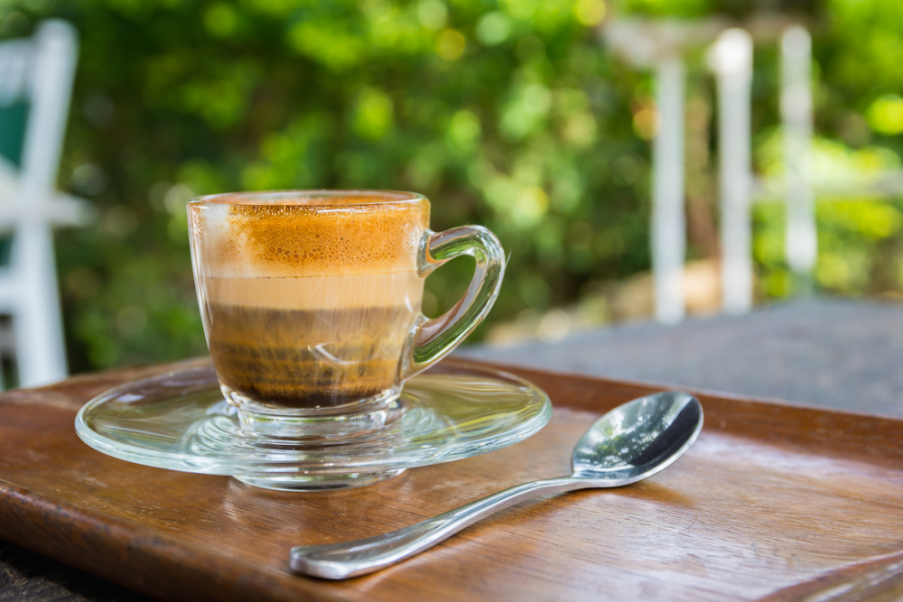 An espresso Macchiato on a table with a spoom