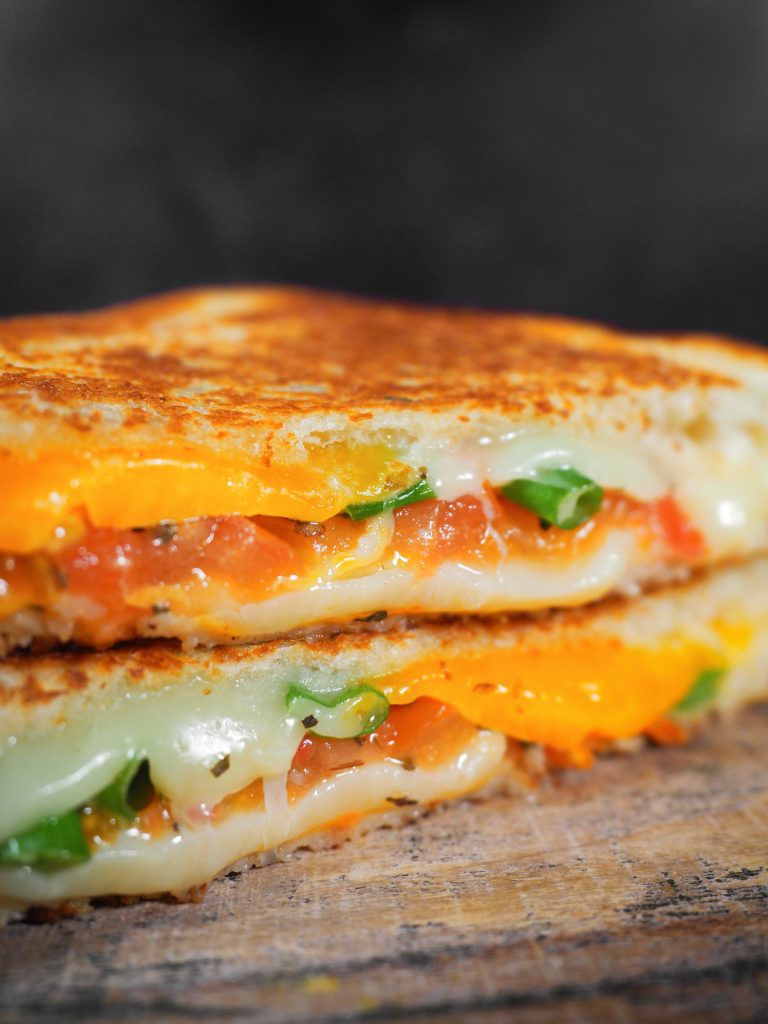 close up photo of grilled cheese with tomato and veggies