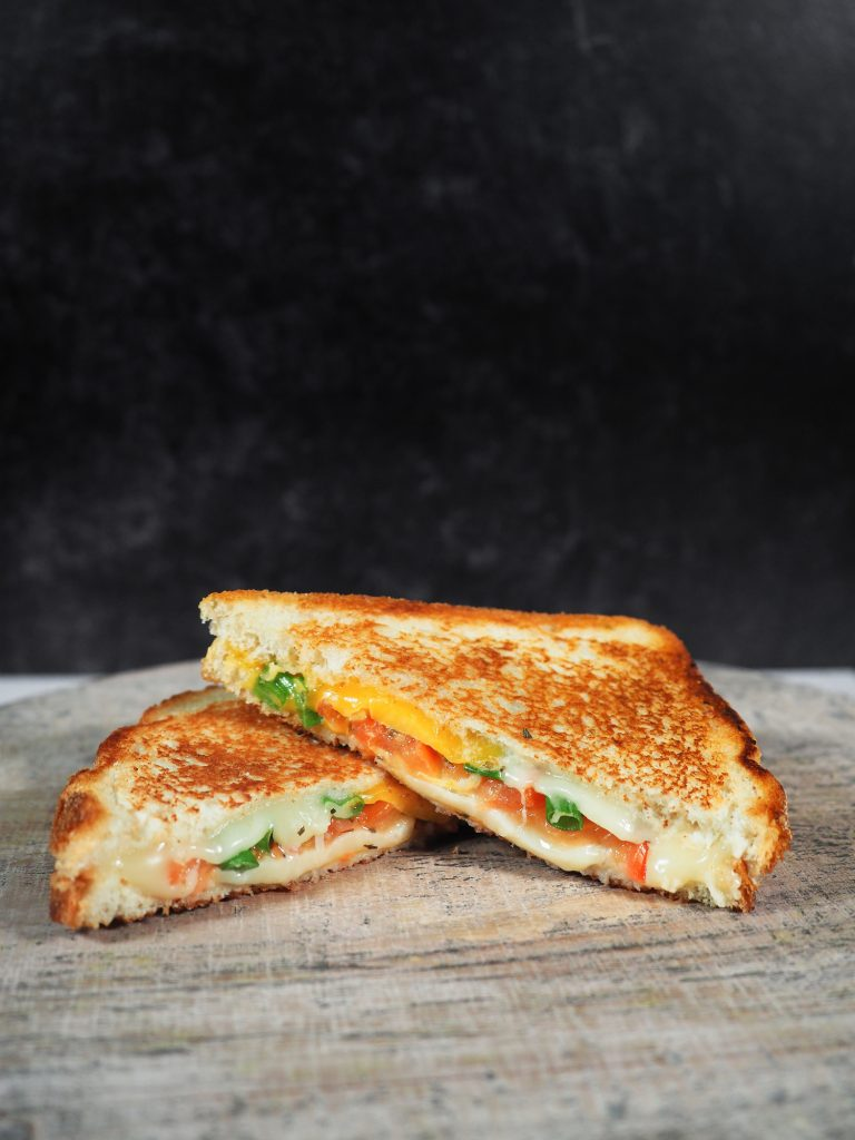 wide photo of grilled cheese with confetti veggies and tomato