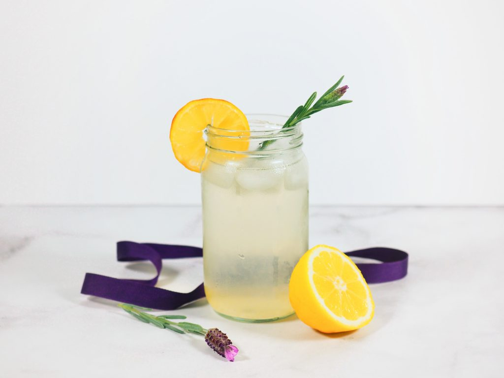 lavender lemonade in glass jar with lemons and lavender on countertop