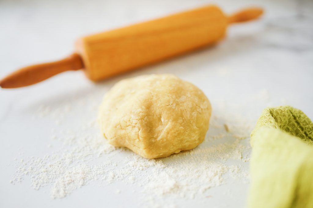 close up photo of pie crust with oil with rolling pin