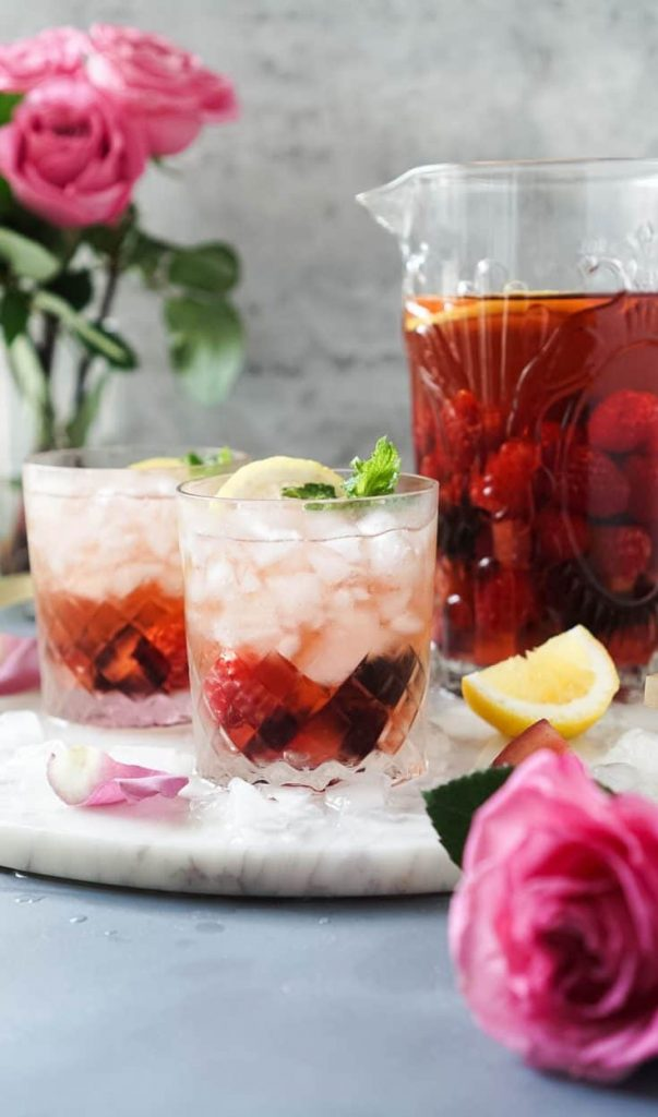 Photo of rose sangria in a large pitcher, also seen are two glasses filled with rose sangria and a garnish of lemon. One of the easy cocktails to make at home.