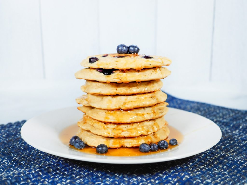 vegan blueberry pancakes on plate with syrup and fruit