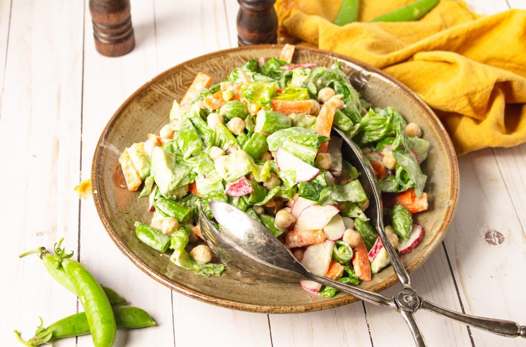 vegan chopped salad on plate with tongs