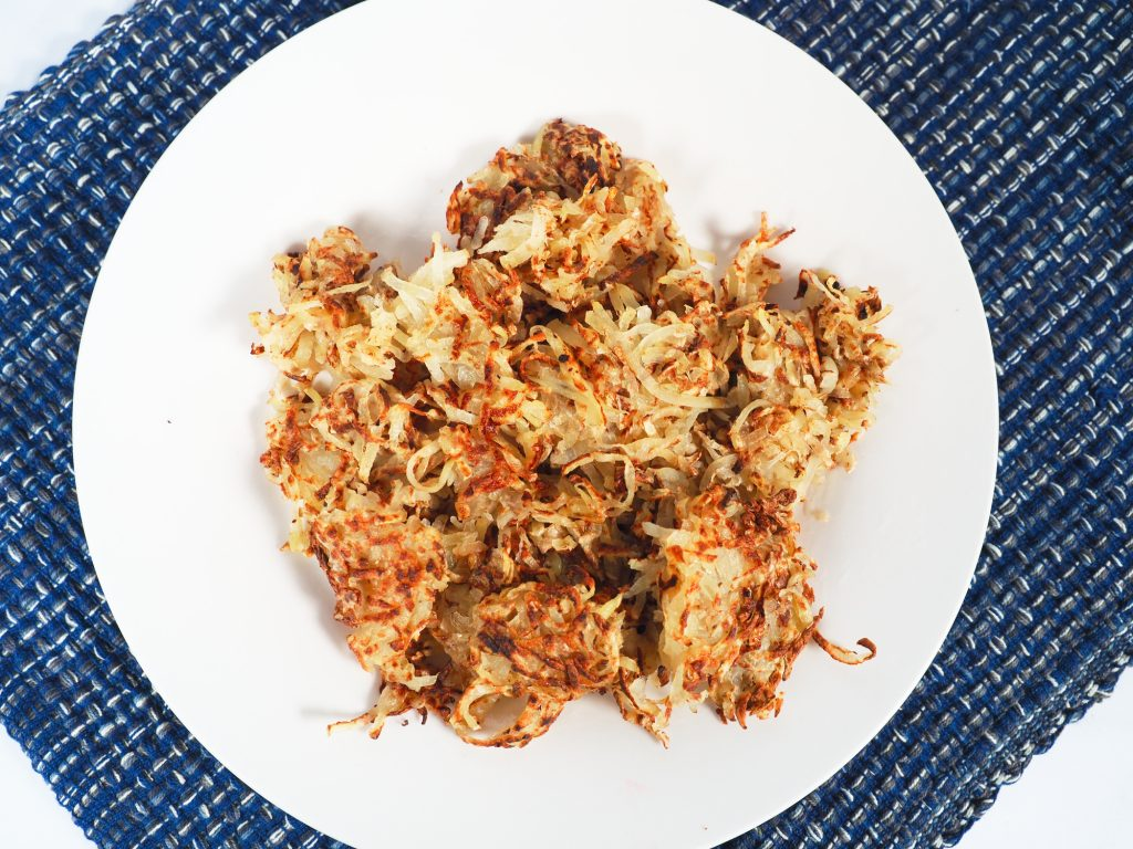 photo of a plate of hashbrowns on a blue mat
