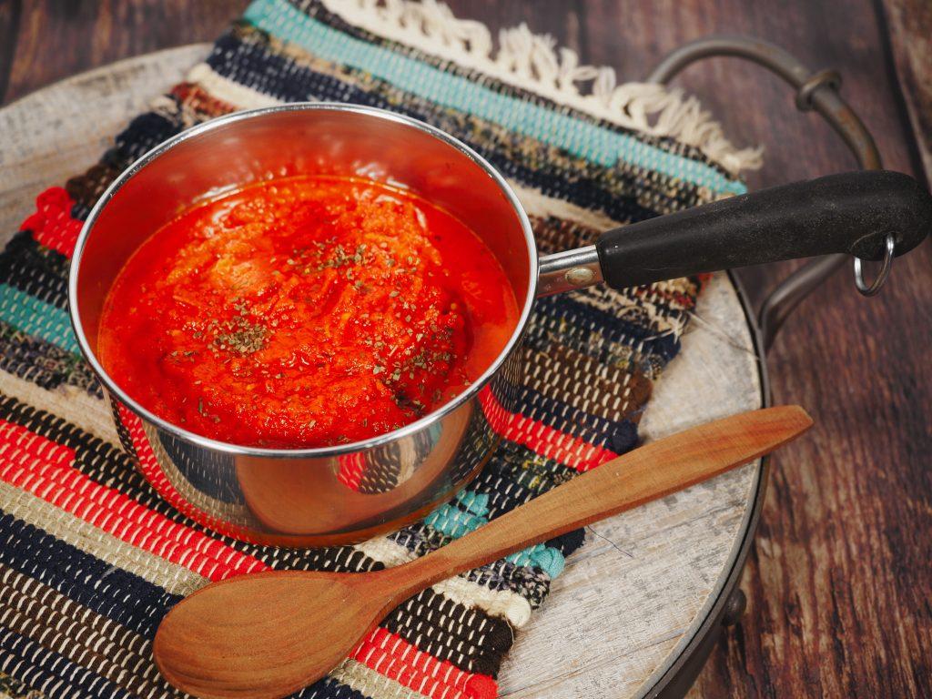 spoon laying next to vegan tomato sauce in pan