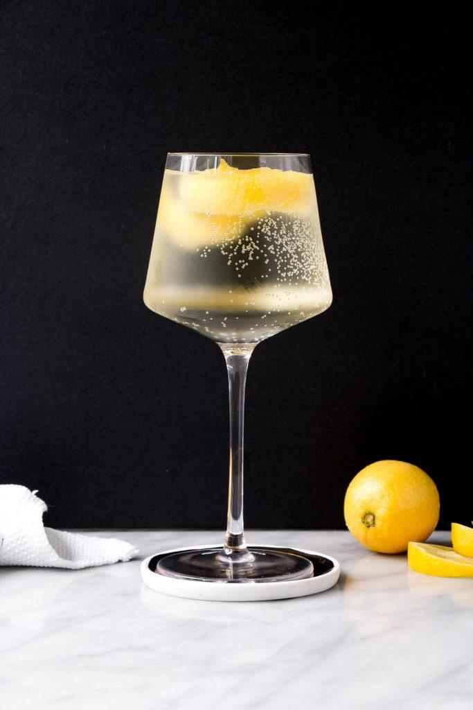 Photo of a white wine spritzer with lemon garnish.