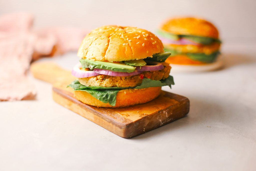 Photo of a 15 minute chickpea burger being served on a wooden board. A vegan Mother's Day recipe for moms that prefer savory over sweet.