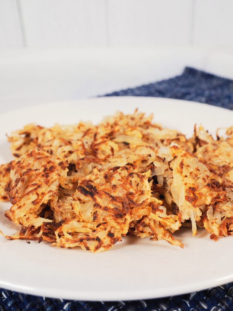 Photo of vegan hash browns being served on a round white plate.