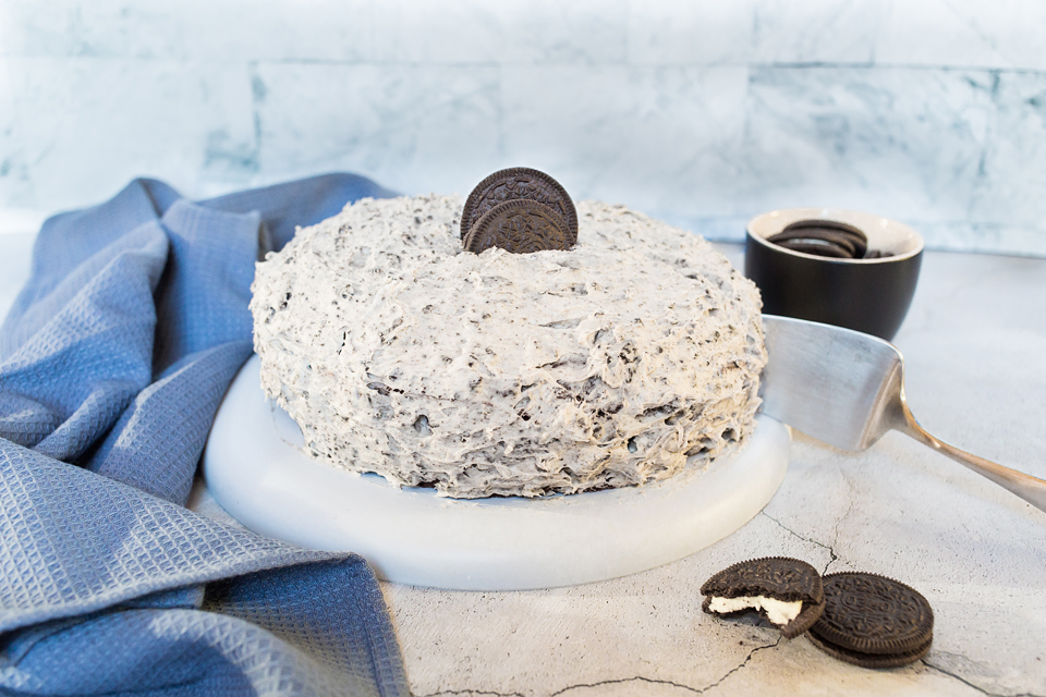 Photo of vegan Oreo cake with buttercream frosting being served on a round white platter.