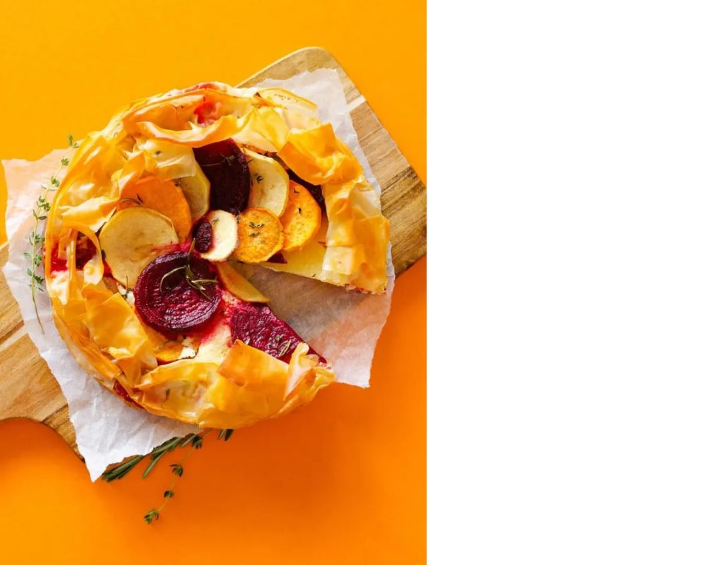 Photo of a savory apple tart with flaky phyllo crust being served on a wooden board.