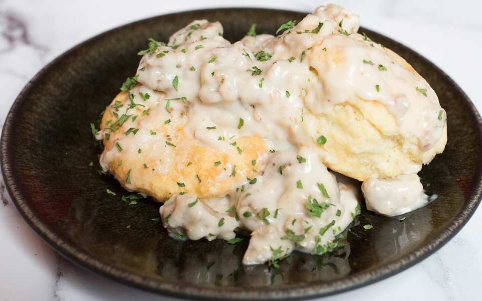 Photo of southern-style vegan biscuits and gravy being served on a dark round plate. One of the ultimate in comfort food vegan Thanksgiving recipes.