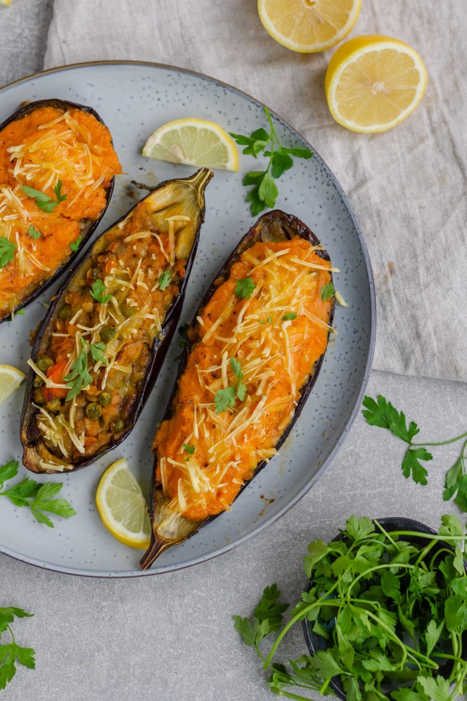 Photo of vegan lentil shepherd's pie stuffed eggplant being served on a speckled round plate.