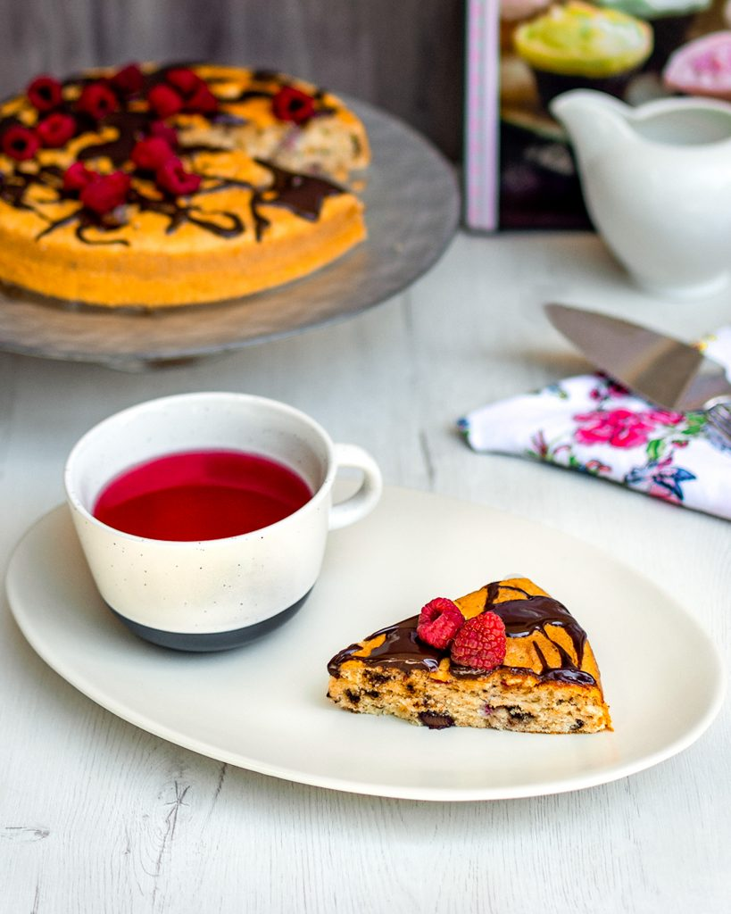 slice of chocolate and raspberry cake with tea