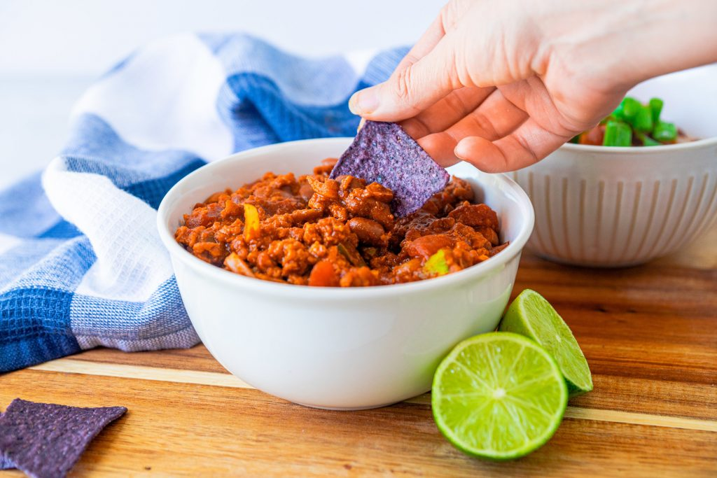 tortilla chip being dipped into easy vegan chili recipe in bowl