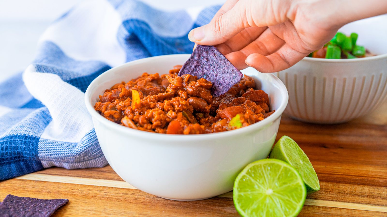 tortilla chip being dunked into vegan chili