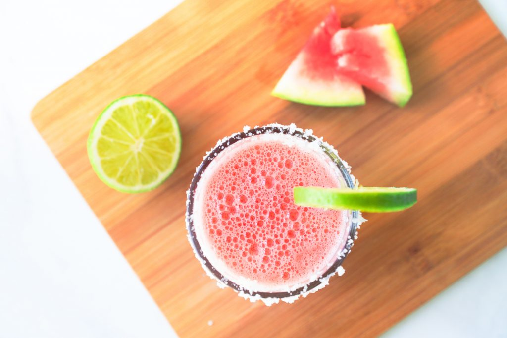 photo of a frozen watermelon margarita on a cutting board with lime and watermelon