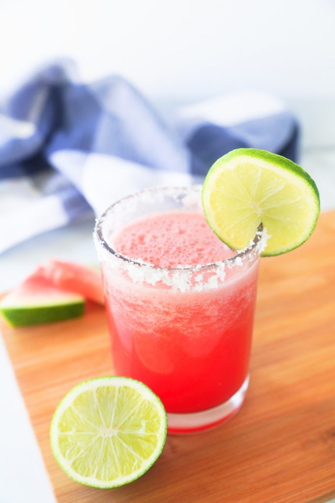 frozen watermelon margarita with fresh limes and blue towel