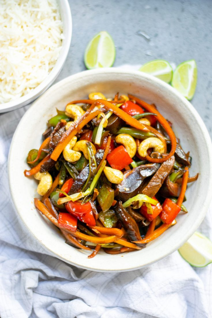 kung pao vegetables in a bowl with limes