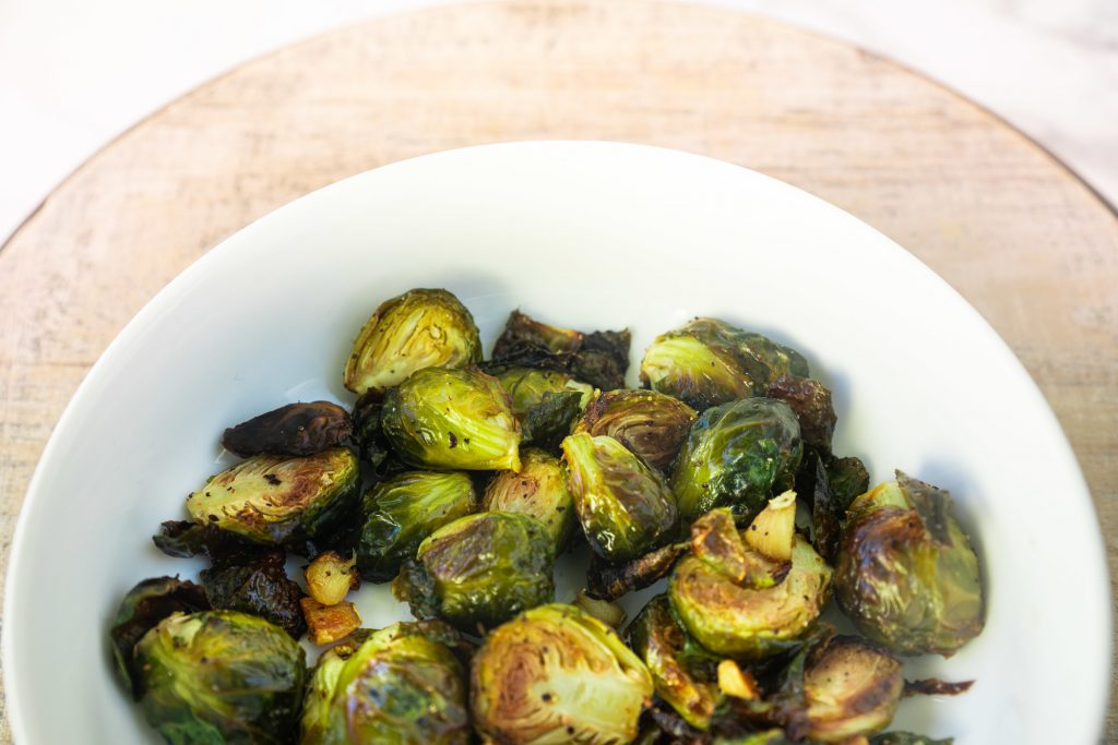 vegan brussels sprouts over a brown serving tray