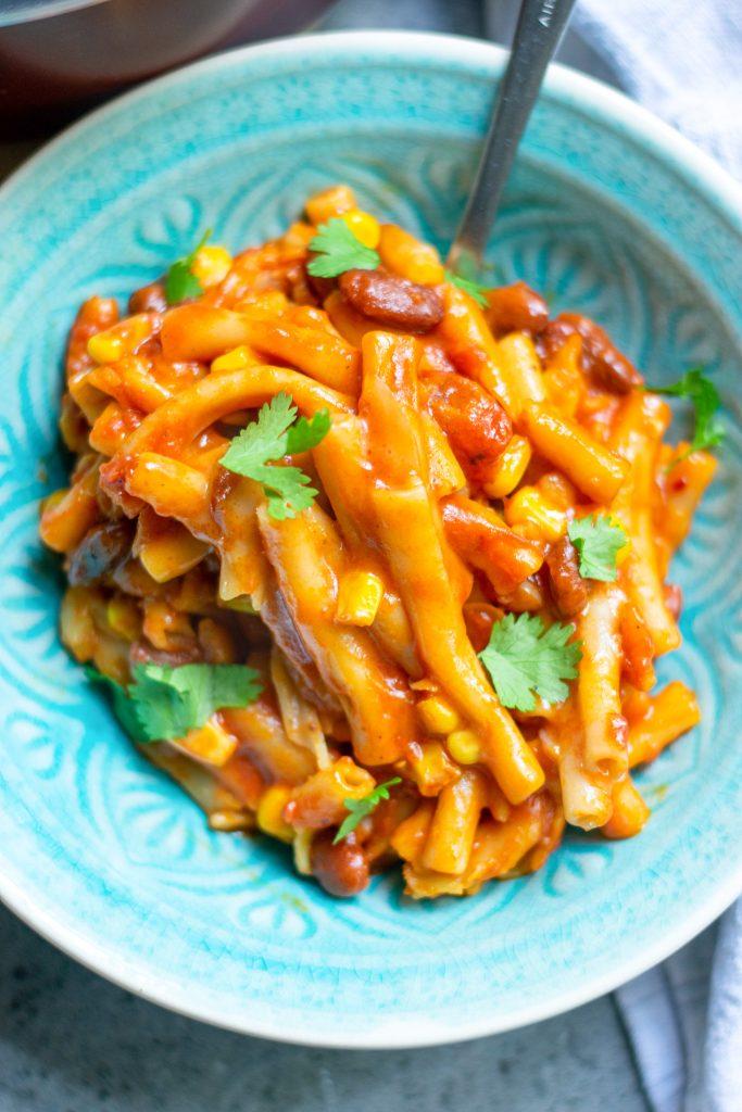 close up image of vegan chili mac with corn, beans and cilantro