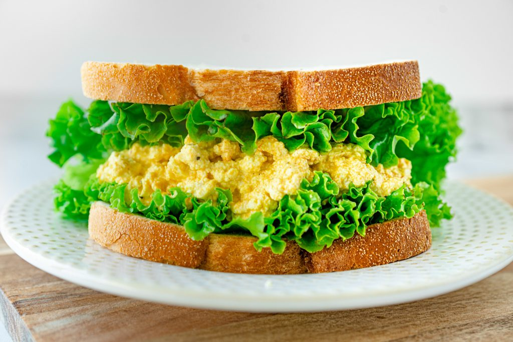 vegan egg salad sandwich on plate with lettuce