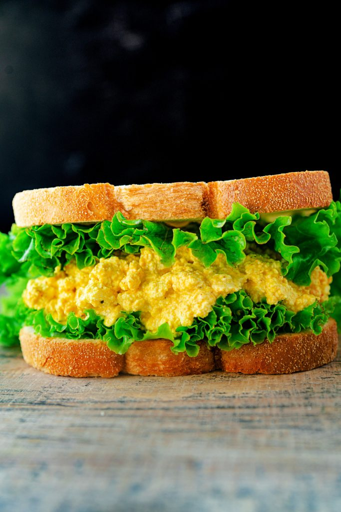 vegan egg salad sandwich on a black background