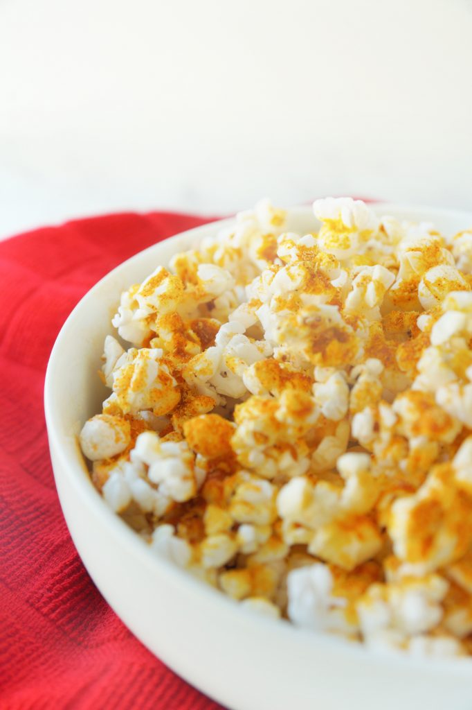 side of a bowl filled with cheesy vegan popcorn