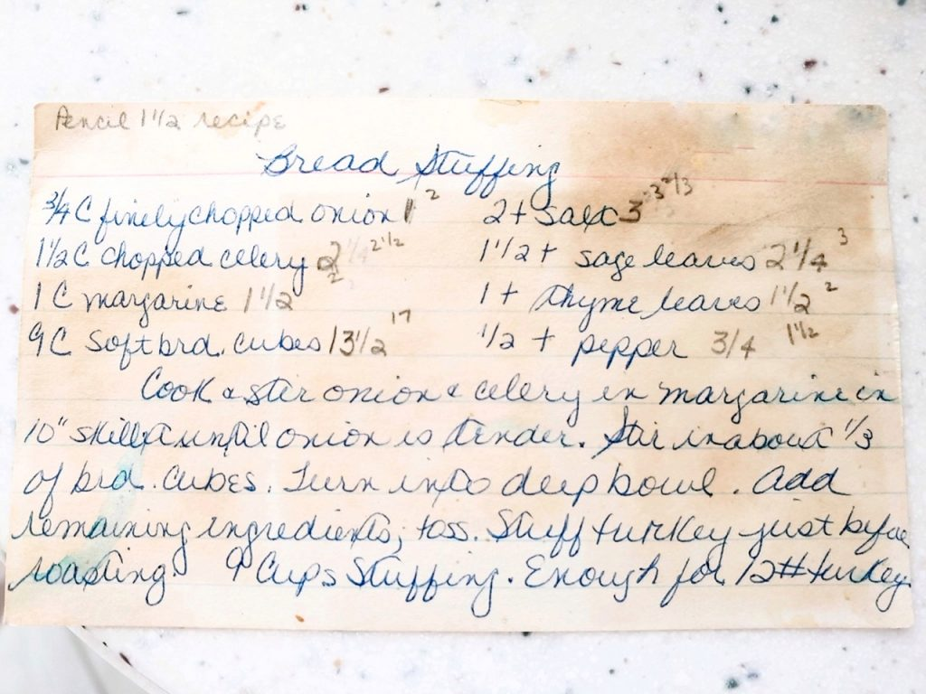 handwritten recipe for bread stuffing stained on a white counter