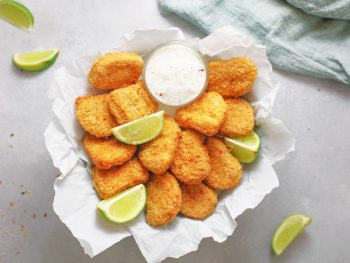 crispy baked vegan tofu nuggets in a bowl with limes