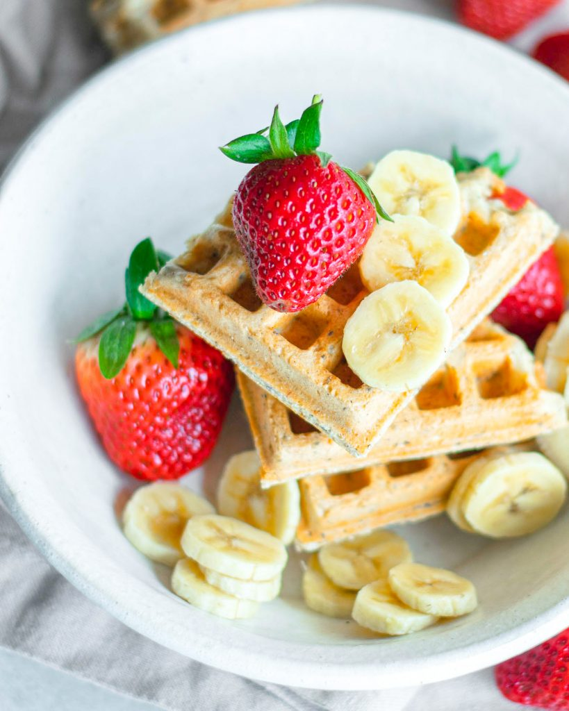 Vegan waffles on white plate with fresh fruit