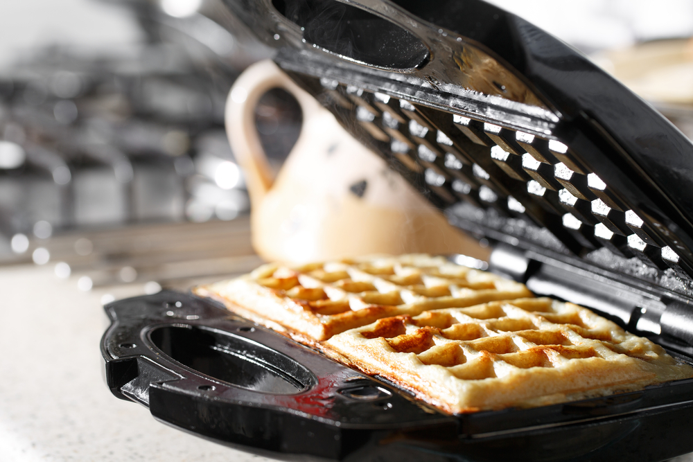 waffle iron with removable plates with vegan waffle cooking on it