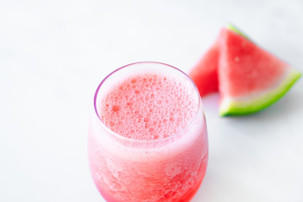 watermelon in the background of a finished watermelon smoothie