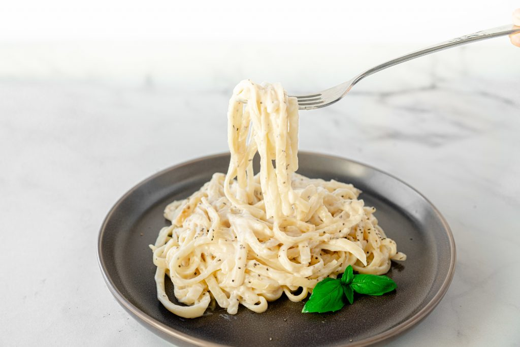 fork picking up vegan alfredo pasta with creamy sauce