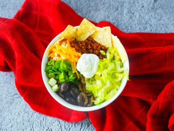 vegan burrito bowl with sour cream and chips