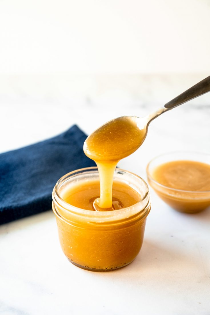 vegan caramel sauce dripping from spoon