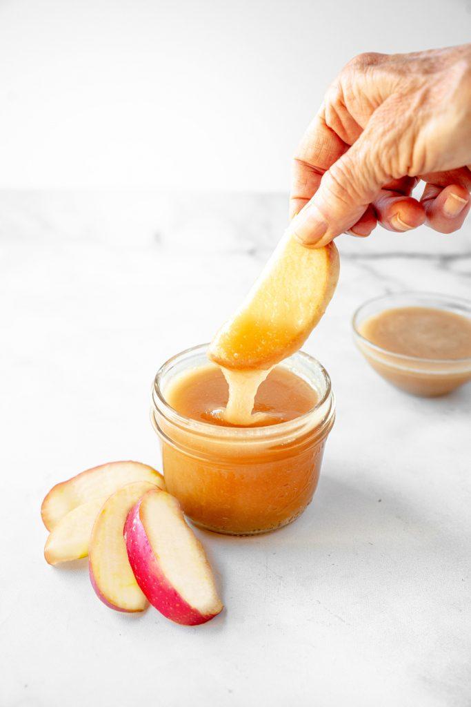 hand dunking apple spice into vegan caramel sauce