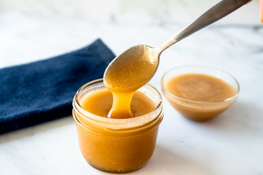 spoon holding vegan caramel sauce with some in the background