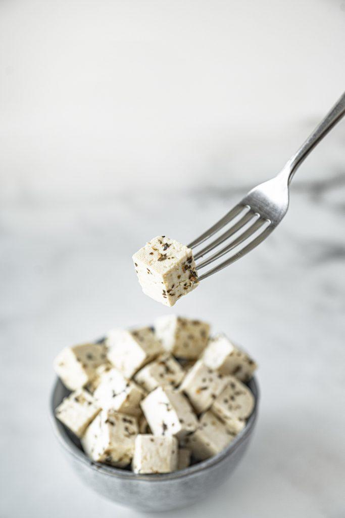 fork holding a slice of tofu feta