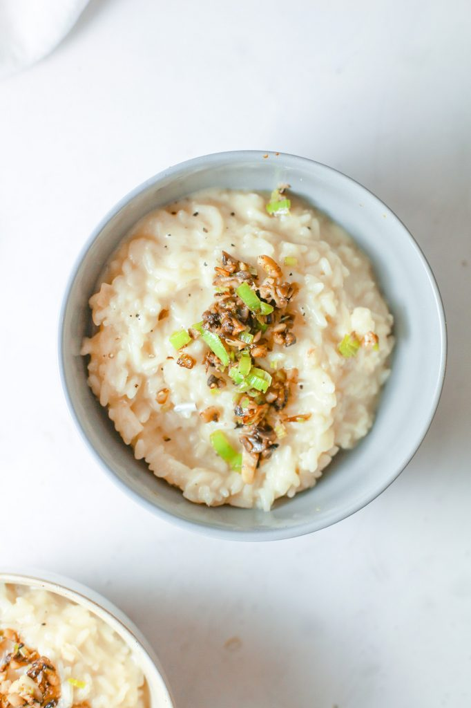 Photo of vegan mushroom risotto being served in a white round bowl.