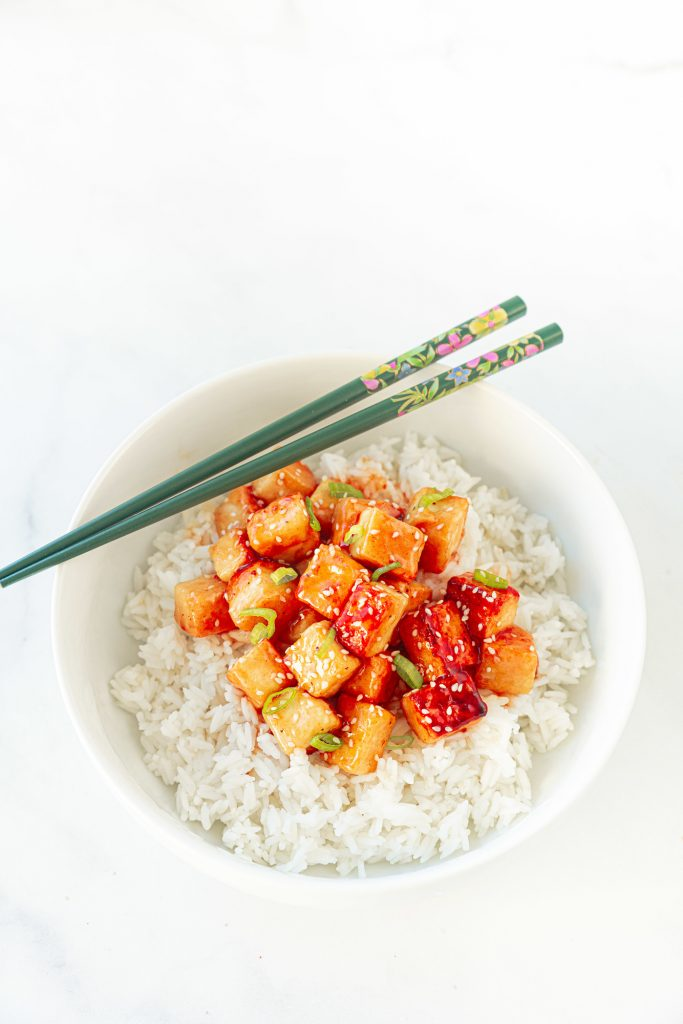 chopsticks resting on the side of a bowl of orange tofu with rice