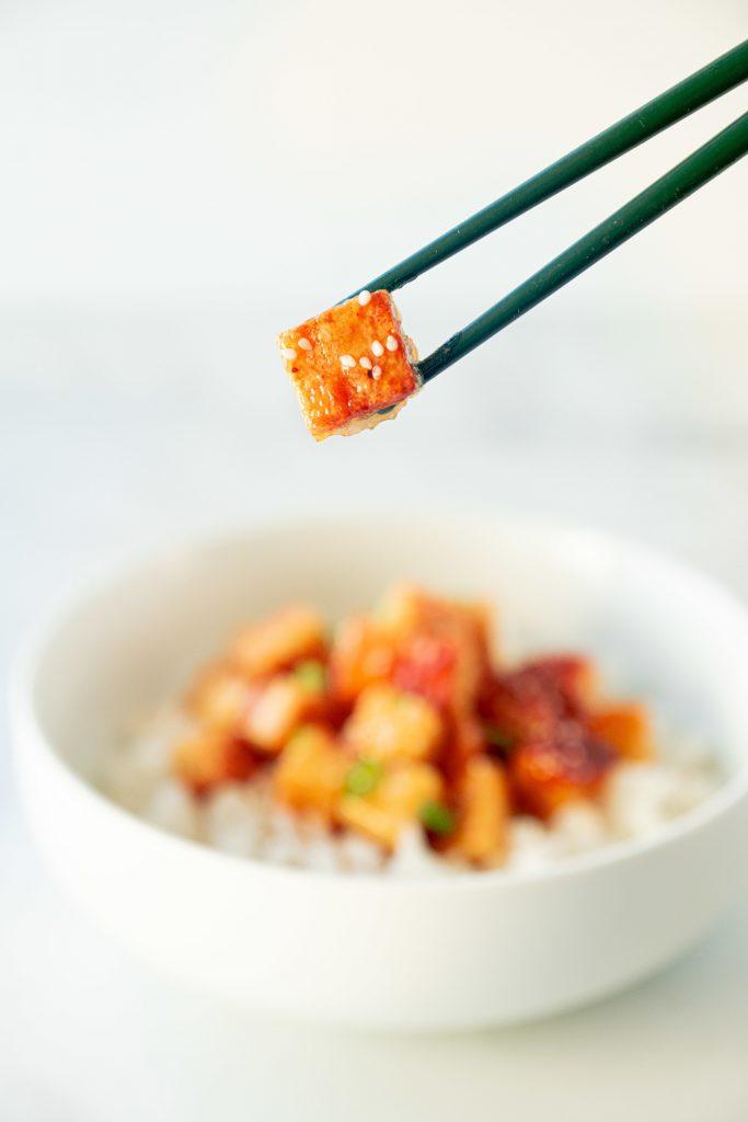 chopsticks picking up a piece of vegan orange chicken