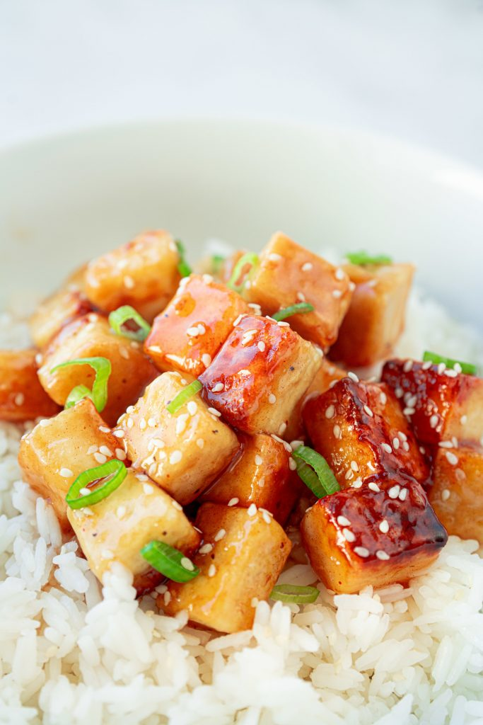 vegan orange tofu in a bowl with rice and green onions