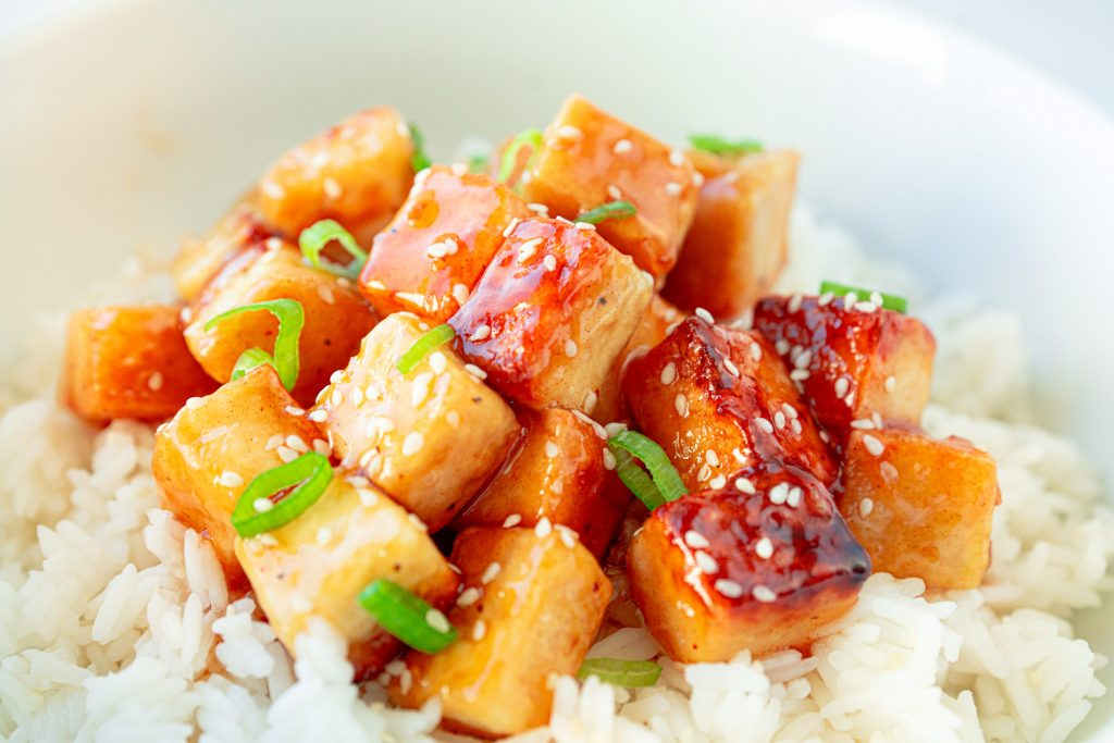 vegan orange tofu over white rice with sesame seeds