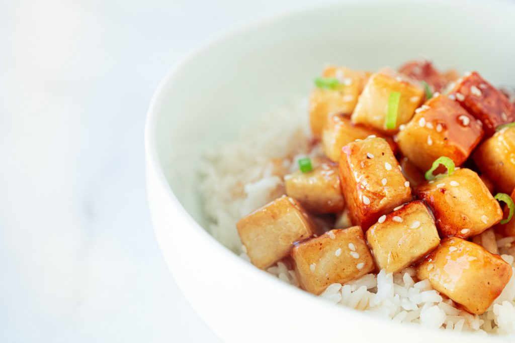 side of a bowl of orange tofu in rice