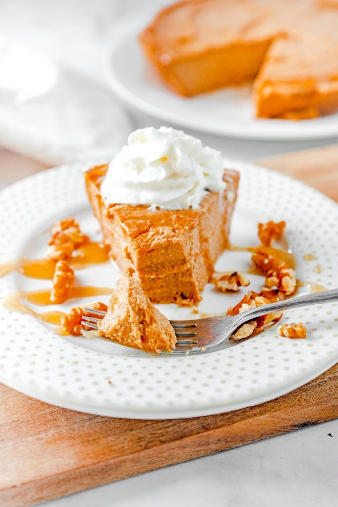 vegan pumpkin cheesecake on plate topped with whipped cream and caramel