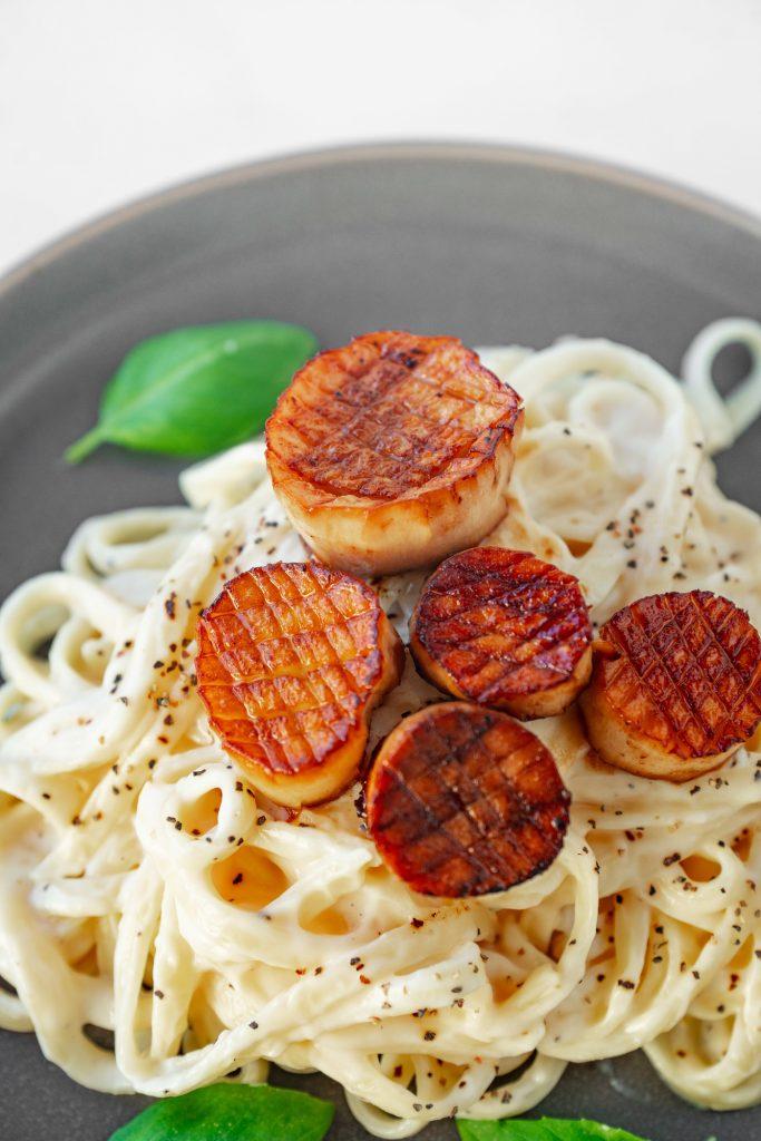 close up of vegan scallops on alfredo pasta