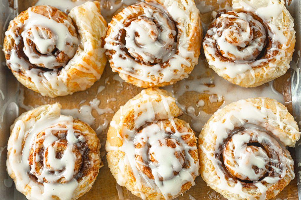 vegan puff pastry cinnamon rolls on baking sheet with glaze