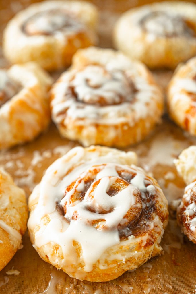 close up of sugar glaze on puff pastry cinnamon buns that are vegan