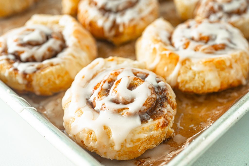 close up photo of puff pastry cinnamon rolls on baking sheet